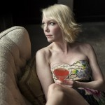 Portrait of a blonde woman drinking a pink martini.